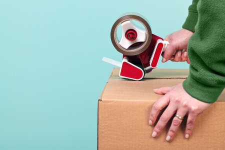Photo of a womans hands taping up a cardboard box, can be used for removal or logistics related themes. photo