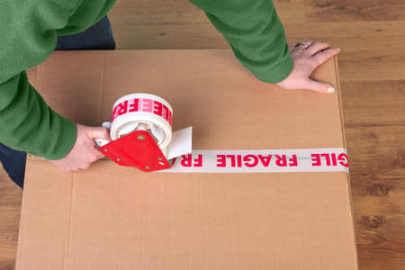 Photo of a womans hands taping up a cardboard box, can be used for removal or logistics related themes. Stock Photo