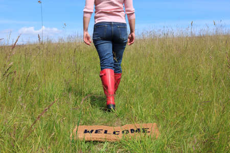 roam: Photo of a woman walking across a welcome mat in a grassy field on a bright sunny day with blue sky. Stock Photo