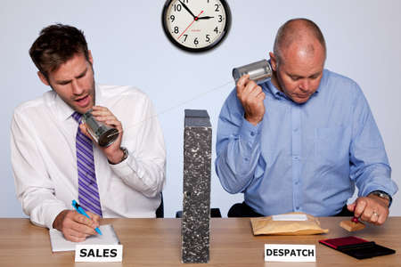 dept: Amusing photo showing the behind the scenes reality of the sales and despatch departments for a small business, both guys sharing the same desk and communicating via a tin can phone. Good image to use for internet shopping related themes. Stock Photo