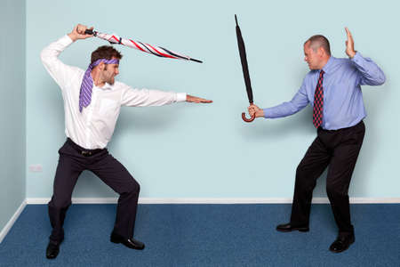 fencing sword: Photo of two businessmen having a sword fight using umbrellas, good image to convey conflict, rivalry or disagreement.