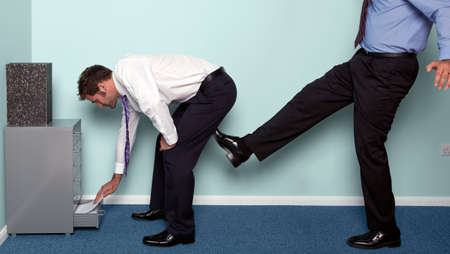 Photo of a businessman bending over to get something out of a drawer as a colleague kicks him up the backside. Stock Photo