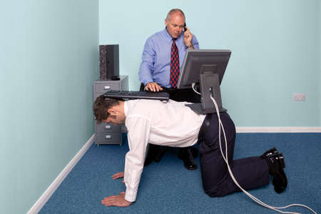 adapt: Photo of a businessman using a work experience employee for his desk Stock Photo