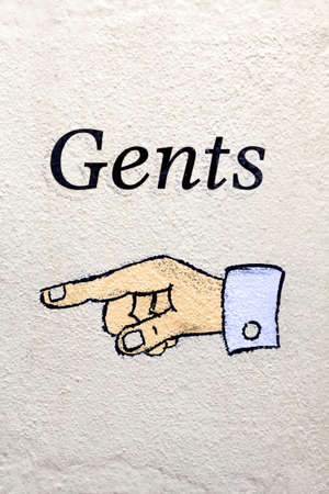 Photo of a Gents sign with a finger pointing the way. photo
