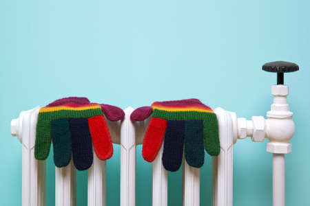 seasonal clothes: Photo of a pair of hand knitted striped woolen gloves drying on an old traditional cast iron radiator.  Stock Photo