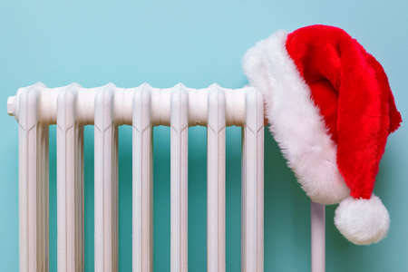 cast iron: Photo of a red and white Father Christmas hat hanging on an old traditional cast iron radiator.