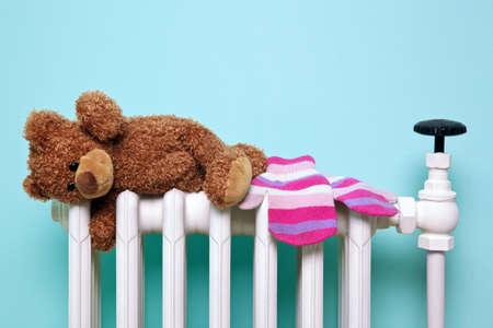 Foto di un bambino teddy orso e guanti di lana asciugatura su un vecchio radiatore tradizionale in ghisa, buona immagine per l'inverno e temi dell'infanzia. L'orso è un generico non-marchio orso, FYI si chiama Bob! Archivio Fotografico