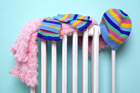 Photo of a girls hat, scarf and gloves drying on an old traditional cast iron radiator, good image for winter related themes.