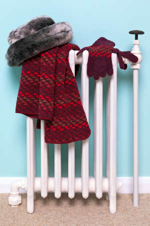 woman's: Photo of a womans hat, scarf and gloves drying on an old traditional cast iron radiator, good image for winter related themes. Stock Photo