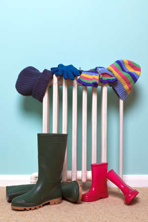 radiador: Foto de sombreros para niños, guantes y botas botas de agua de secado por un viejo radiador tradicional de hierro fundido en el pasillo, buena imagen para los temas relacionados con la infancia de invierno.