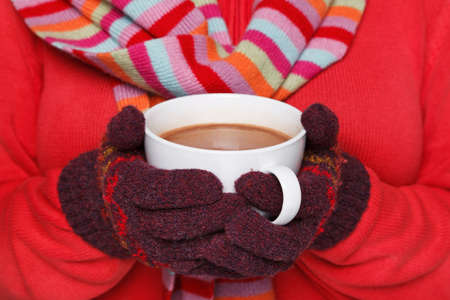 Close up midriff photo of a woman wearing a red jumper, woolen gloves and a scarf holding a mug full of hot chocolate, good image to convey a feeling of winter and warmth. Stock Photo