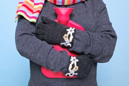 Foto einer Frau mit einem roten Wärmflasche auf die Brust, während das Tragen der Hand kniited Wollhandschuhe versuchen, warm, gutes Bild für den Winter Krankheit oder Wärme verwandten Themen zu halten. Standard-Bild