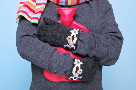 warming: Photo of a woman holding a red hot water bottle to her chest whilst wearing hand kniited woolen gloves trying to keep warm, good image for winter illness or warmth related themes. Stock Photo