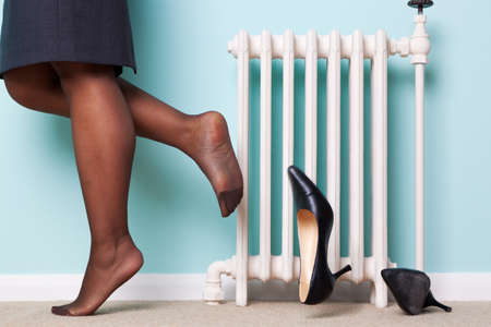 stockings feet: Photo of a businesswomans legs with stockings on kicking her high heel shoes off as she returns home after a hard day at work. Motion blur on one of the shoes. Stock Photo