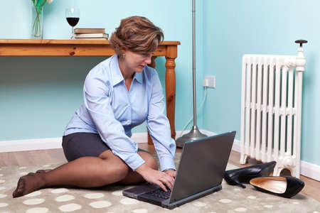 Photo of a businesswoman sitting on a rug at home working on her laptop with her shoes off and a glass of red wine on the table. photo