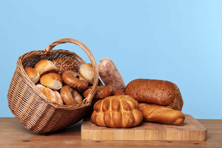 Photo of various types of bread loaves and rolls in a wicker basket on a wooden table with blue background. photo