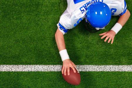 Overhead photo of an American football player making a one handed touchdown. The uniform he's wearing is one I had made using my name and does not represent any actual team colours. photo