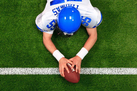 Overhead photo of an American football player making a touchdown with both hands on the ball. The uniform hes wearing is one I had made using my name and does not represent any actual team colours. photo