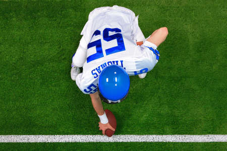 touchdown: Overhead photo of an American football player center offense about to snap the ball. The uniform hes wearing is one I had made using my name and does not represent any actual team colours.