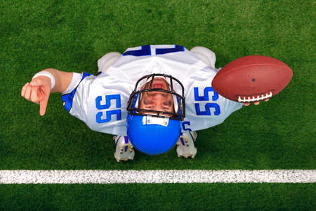 Overhead photo of an American football player making a touchdown celebration looking up in the air with his finger raised. The uniform hes wearing is one I had made using my name and does not represent any actual team colours.