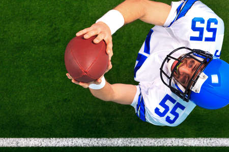 touchdown: Overhead photo of an American football player wide receiver catching the ball in the air. The uniform hes wearing is one I had made using my name and does not represent any actual team colours.