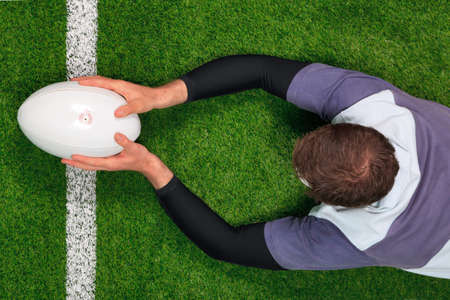 elevated view: Overhead photo of a rugby player diving over the line to score a try with both hands holding the ball. Stock Photo