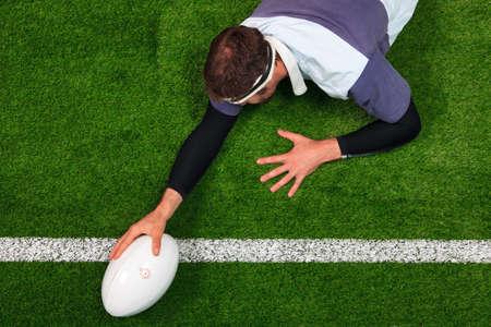 pelota de rugby: Foto aérea de un jugador de rugby se extiende sobre la línea para marcar un try con una mano sobre el balón. Foto de archivo