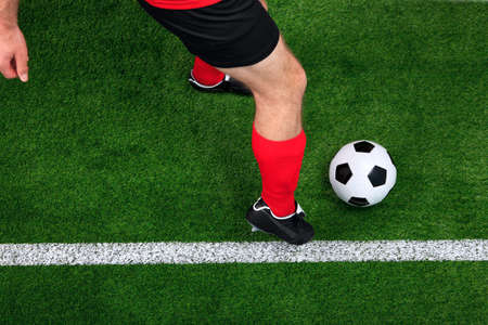 Overhead photo of a football or soccer player dribbling with the ball on the sideline photo