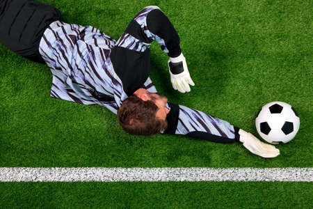 Overhead photo of a football goalkeeper diving to save the ball from crossing the goal line.