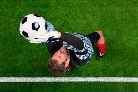 Overhead photo of a football goalkeeper jumping in the air saving the ball on the line. Focus point is on his face. photo