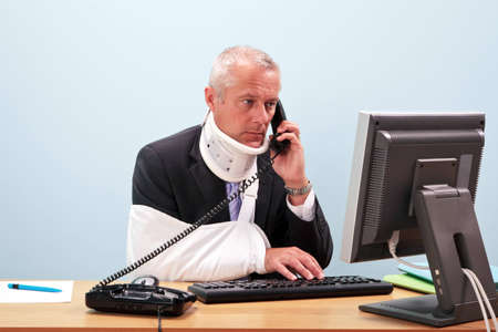 lesionado: Foto de un hombre de negocios maduros con lesiones de hablar por tel�fono mientras que intenta trabajar en su equipo. Buena imagen de seguridad y salud o accidente en temas relacionados al trabajo.