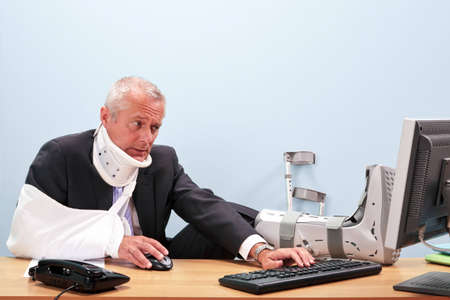 accidente trabajo: Foto de un hombre de negocios maduro, con múltiples lesiones sentado en su escritorio tratando de trabajar en su equipo. Buena imagen de seguridad y salud, seguro de accidente de trabajo o temas relacionados con la salud.