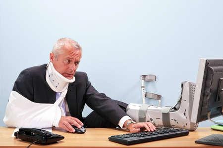 maladroit: Photo d'un homme d'affaires mature avec de multiples blessures assis � son bureau du mal � travailler sur son ordinateur. Bonne image pour la sant� et la s�curit�, l'assurance accident de travail ou des th�mes de la sant� connexes. Banque d'images