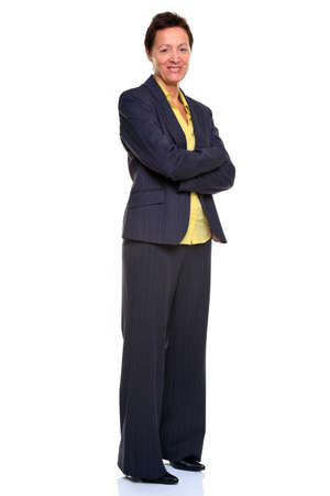 Photo of a mature businesswoman with her arms folded stood sideways smiling to camera, full length, isolated on a white background.