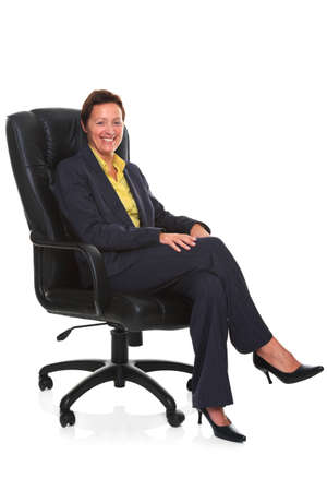 crossed legs: Photo of a mature businesswoman wearing a smart trouser suit, sat in a leather executive chair with her legs crossed and smiling to camera, isolated on a white background with natural chair relection. Stock Photo