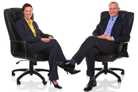 Photo of a mature businessman and businesswoman both sat in a leather executive chairs with their legs crossed and smiling to camera, isolated on a white background with natural chair relection. photo