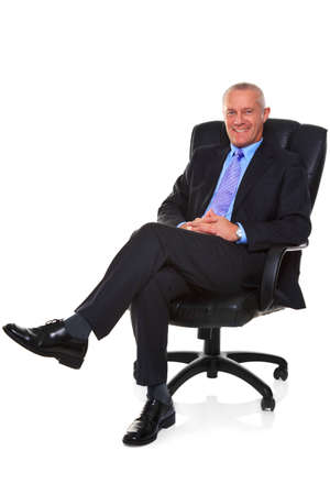 Photo of a mature businessman wearing a smart suit and tie, sat in a leather executive chair with his legs crossed and smiling to camera, isolated on a white background with natural chair relection. Stock Photo
