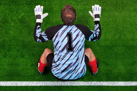 portero: Foto a�rea de un portero de f�tbol de pie en la l�nea de meta en la posici�n de preparado para hacer frente a un tiro penal.