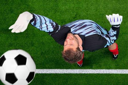 portero: Foto aérea de un portero de fútbol desaparecidos de ahorro de la pelota, ya que cruza sobre la línea. Ligero desenfoque de movimiento en la bola, se centra en su rostro.