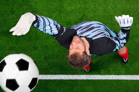 savings goals: Overhead photo of a football goalkeeper missing saving the ball as it crosses over the line. Slight motion blur on the ball, focus is on his face.