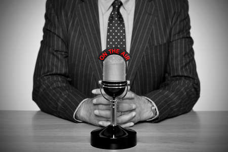 Photo of a news broadcaster sat at a desk and retro microphone with an On The Air illuminated sign, converted to B&W retaining the colour of the text and added vignette for a vintage look. Stock Photo - 11211837