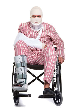 leg injury: Photo of a man with various injuries wearing striped pyjames and sitting in a wheelchair. Stock Photo