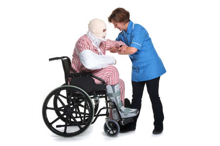 Photo of an hospital patient with multiple injuries being helped by a female nurse. Isolated on a white background. photo
