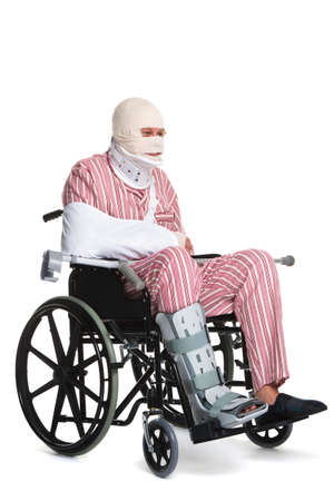 Photo of a man with various injuries wearing striped pyjames and sitting in a wheelchair. photo