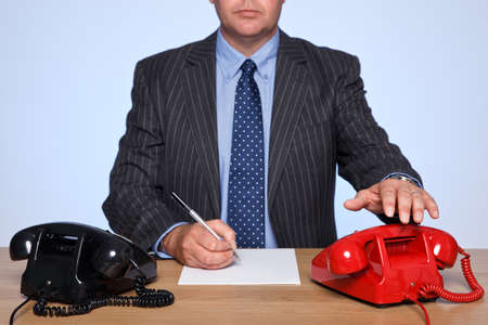 Photo of a businessman sat at a desk with two traditional telephones, one red and one black. His hand is reaching for the red phone. photo