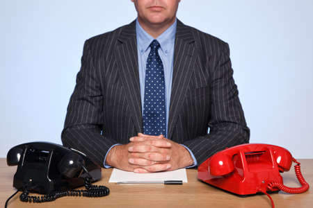 Photo of a businessman sat at a desk with two traditional telephones, one red and one black. photo