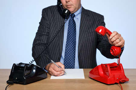 Photo of a businessman sat at a desk with two traditional telephones, one red and one black. He is listening to one call whilst picking up the other phone. photo
