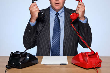 Photo of a businessman sat at a desk with two traditional telephones, one red and one black. Both handsets are raised and he doesn't know who to talk to first. Stock Photo - 11329661