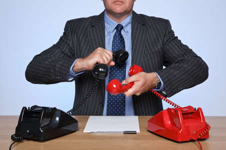 Photo of a businessman sat at a desk with two traditional telephones, one red and one black. Conference call concept. Stock Photo - 11329653