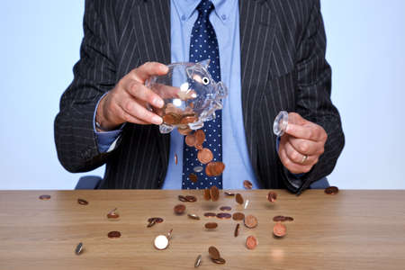 hard times: Photo of a banker sat at his desk emptying coins from his piggy bank.